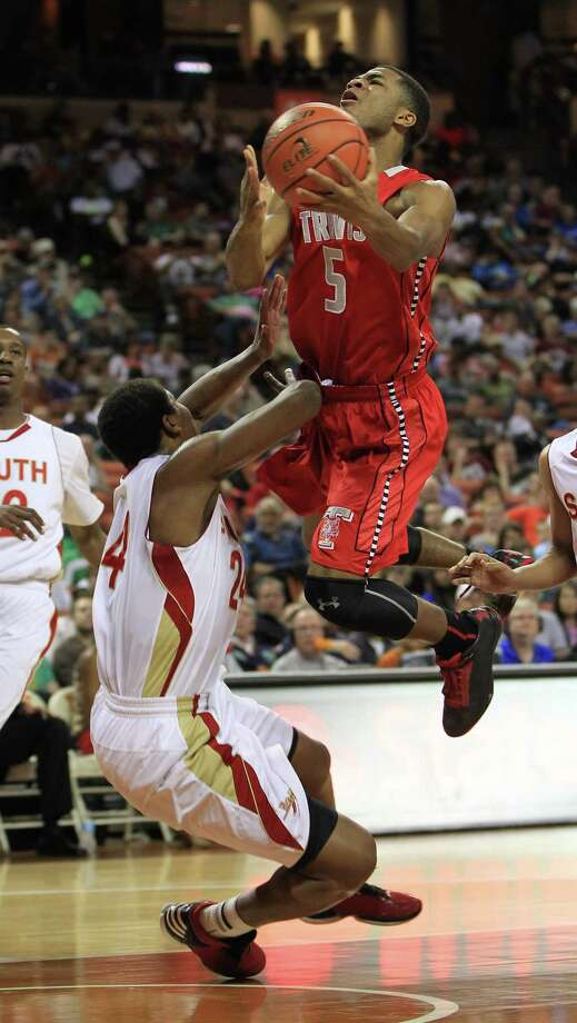 Travis' Andrew Harrison (5) jumps up and over South Grand Prairie's Rick Curry (24) during the first half of the UIL 5A boys state basketball championship game between Fort Bend Travis and South Grand Prairie at the Frank Erwin Center, Saturday, March 9, 2013, in Austin. Photo: Karen Warren, Houston Chronicle / © 2013 Houston Chronicle