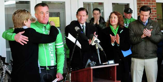 Lynn Mc Donnell, left, hugs her husband Chris Mc Donnell, as he speaks before Team 26 and supporting riders leave Reed Intermediate School in Newtown, Conn. Saturday, March 9, 2013 on the Sandy Hook Ride to Washington, D.C., to support gun control legislation. The Mc Donnell's lost their daughter Grace in the Sandy Hook shootings. Photo: Michael Duffy / The News-Times