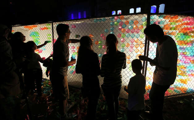 Kids produce their own artwork in a backlit fence as they place translucent cups in a pattern as Luminaria is held in downtown San Antonio on March 9, 2013. Photo: Tom Reel, San Antonio Express-News