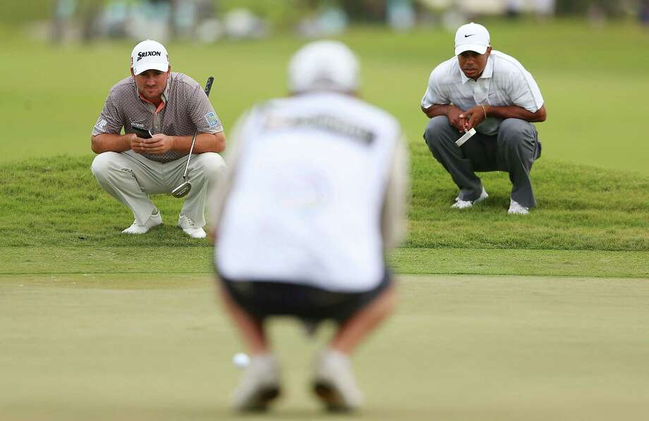 Graeme McDowell, left, did his best to remain within striking distance of Tiger Woods, right, who racked up seven more birdies Saturday. Photo: Mike Ehrmann, Staff / 2013 Getty Images