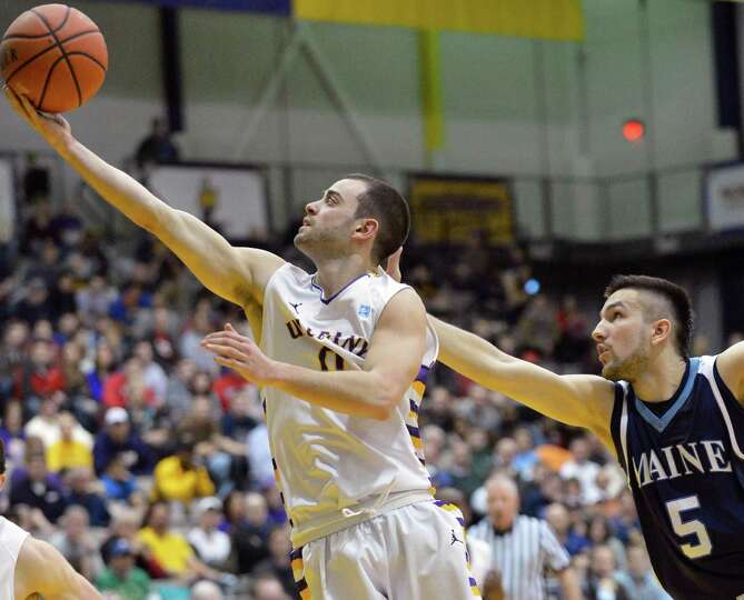 UAlbany's #0 Jacob Iati sails past  Maine's #5 Zarko Valjarevic on his way to the basket during thei