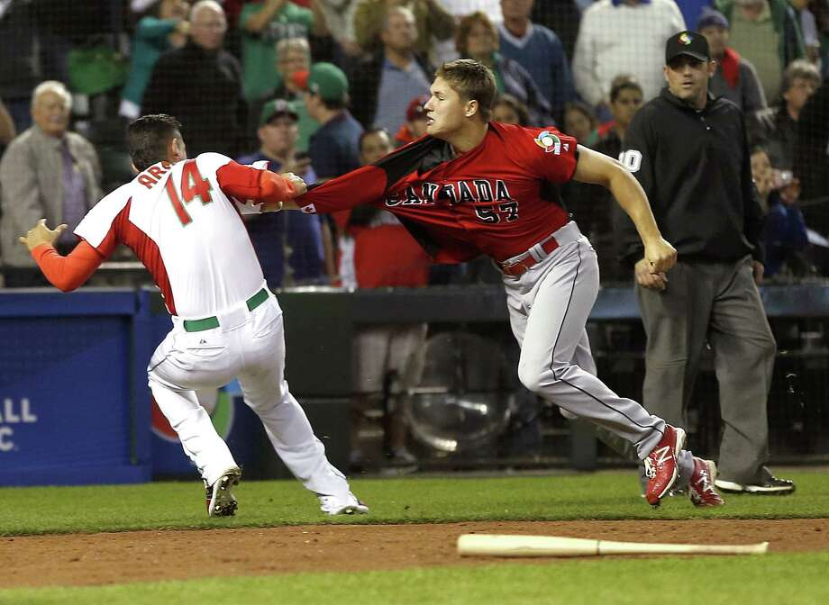 Canada's Jay Johnson (right) and Mexico's Eduardo Arredondo go after each other in a huge fight that broke out during the ninth inning of Canada's 10-3 victory Saturday. Seven players ended up getting ejected. Photo: Matt York / Associated Press