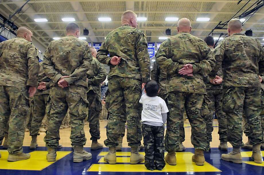 RETRANSMISSION TO CORRECT CHILDS RELATIONSHIP - 3-year-old Seth Byers  holds the hand of his grandfather Chief Warrant Officer 3 Todd King,  for the first time as more than 160 local soldiers from the 507th Engineer Battalion returned home during a homecoming event at Portage, Mich. Central High School's gymnasium, Saturday, March 9, 2013 after a 10-month deployment in Afghanistan. (AP Photo/Kalamazoo Gazette-MLive Media Group, Matt Gade) ALL LOCAL TV OUT; LOCAL TV INTERNET OUT Photo: Matt Gade, Associated Press