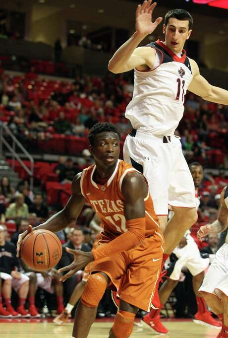 Texas guard Myck Kabongo, driving past Texas Tech's Dejan Kravic, was 0 for 12 from the field, but he made seven free throws and had four assists. Photo: Zach Long / Lubbock Avalanche-Journal