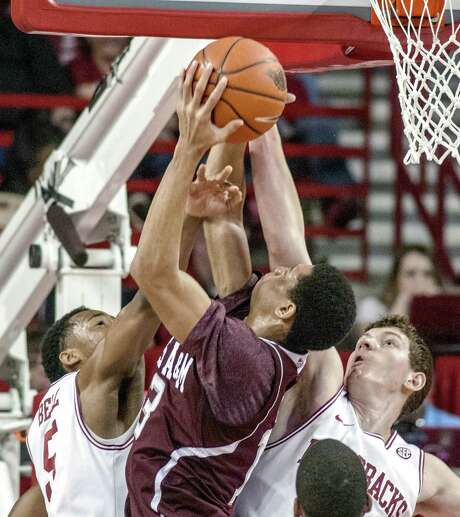 Arkansas' Hunter Mickelson blocks a shot attempt by Texas A&M's Jordan Green in the first half. Green scored 14 points in the game, almost 12 more than his season average. Photo: April Brown / Associated Press