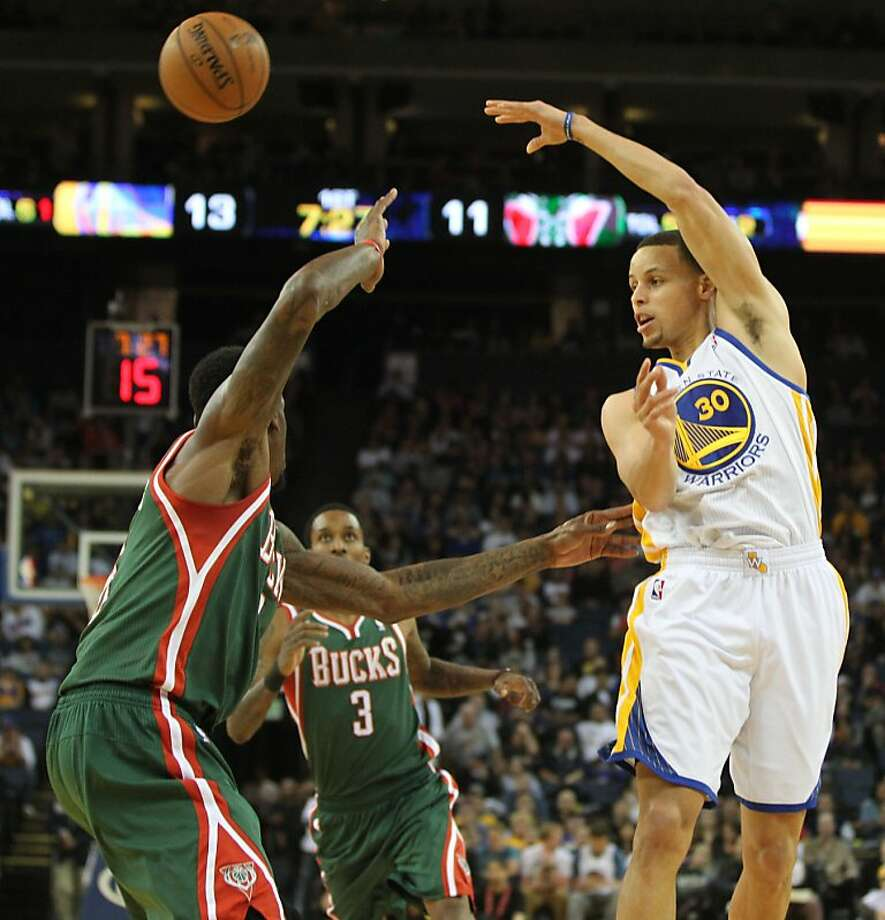 Stephen Curry (right) passes over Milwaukee defenders. Curry had 10 assists and 16 points. Photo: Lance Iversen, The Chronicle