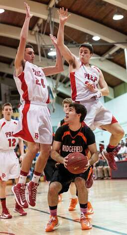 Fairfield Prep's Chris Kelly and Quinn Lincoln try to keep Ridgefield high school's Daniel Greenberg from going up for a shot in a quarterfinal round 2013 CIAC class LL boys basketball tournament game held at Alumni Hall, Fairfield University, Fairfield CT on Saturday March 9th 2013. Photo: Mark Conrad / Connecticut Post Freelance