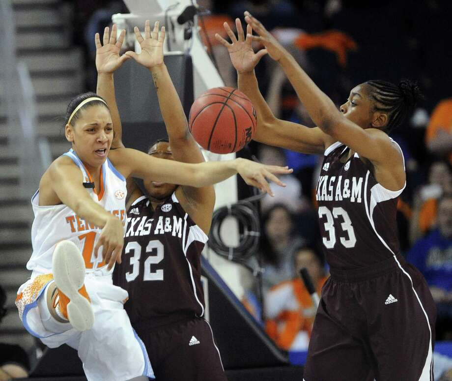 Tennessee forward Cierra Burdick (left) passes as A&M guards Adrienne Pratcher (32) and Courtney Walker (33) apply defensive pressure. Walker led A&M with 18 points. Photo: John Amis / Associated Press