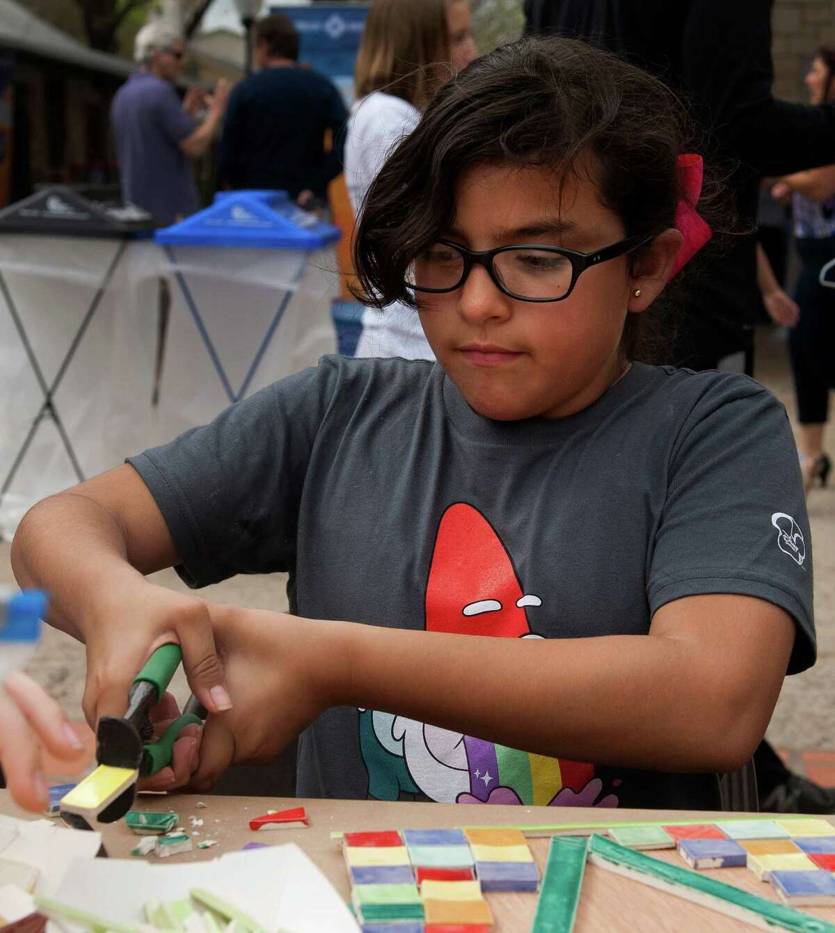10 year-old Valentina Veliz, daughter of Coral Veliz of San Antonio cuts into a piece of tile as she builds a mosaic piece during the S.M.A.R.T. (Supporting Multiple Arts Resources Together) third annual Pie to the People at the historic La Villita March 9, 2013.