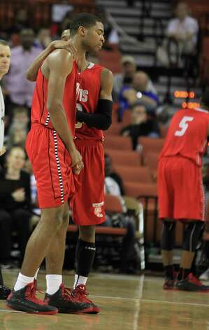 Fort Bend Travis' Aaron Harrison (2) is consoled after he fouled South Grand Prairie's Ben Emelogu (15) on a three-point basket in the final seconds during the second half of the UIL 5A boys state basketball championship game between Fort Bend Travis and South Grand Prairie at the Frank Erwin Center, Saturday, March 9, 2013, in Austin. Travis won the game. Photo: Karen Warren, Houston Chronicle / © 2013 Houston Chronicle