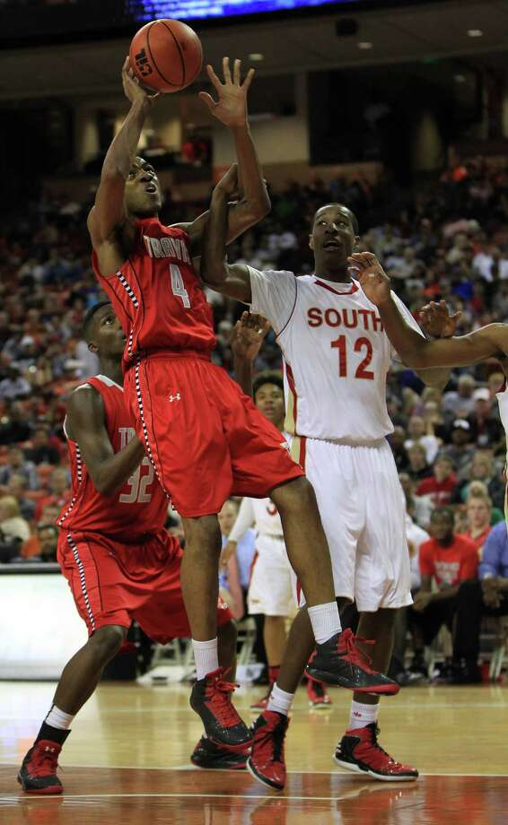 Fort Bend Travis' Daniel Chika gets snagged by South Grand Prairie's Cameron McGriff (12) during the second half of the UIL 5A boys state basketball championship game between Fort Bend Travis and South Grand Prairie at the Frank Erwin Center, Saturday, March 9, 2013, in Austin. Travis won the game. Photo: Karen Warren, Houston Chronicle / © 2013 Houston Chronicle