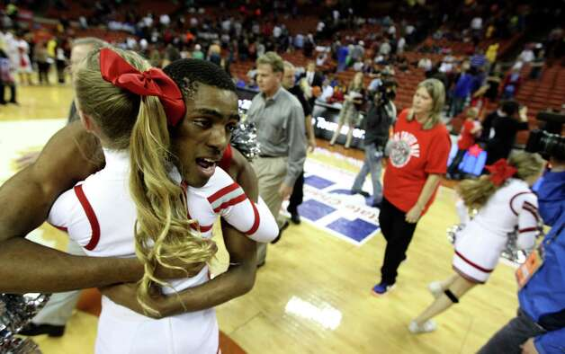Travis Daniel Chika (4) hugs a cheerleader after their win over South Grand Prairie. Photo: Karen Warren, Houston Chronicle / © 2013 Houston Chronicle