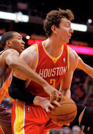 Wesley Johnson of the Suns tries to steal the ball from Omer Asik of the Rockets. Photo: Paul Connors