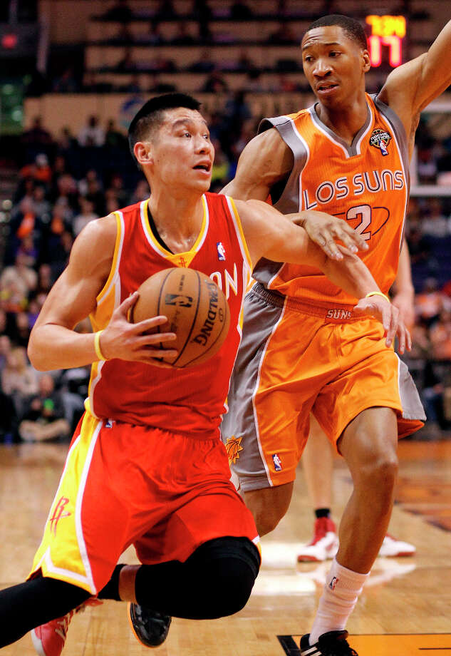 Rockets point guard Jeremy Lin drives to the basket against Wesley Johnson of the Suns. Photo: Paul Connors