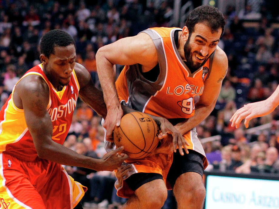 Suns center Hamed Haddadi fights for possession with Patrick Beverley of the Rockets. Photo: Paul Connors