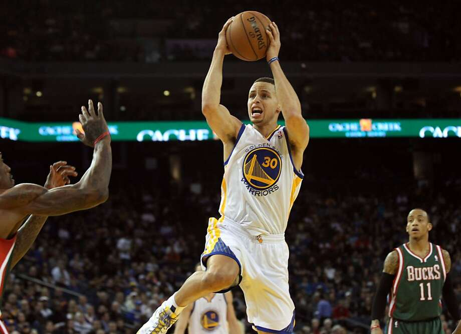 Golden State Warriors guard Stephen Curry (30) shoots between two Milwaukee Bucks defenders in the first half of their NBA basketball game Saturday, March 9, 2013, in Oakland Calif. Photo: Lance Iversen, The Chronicle