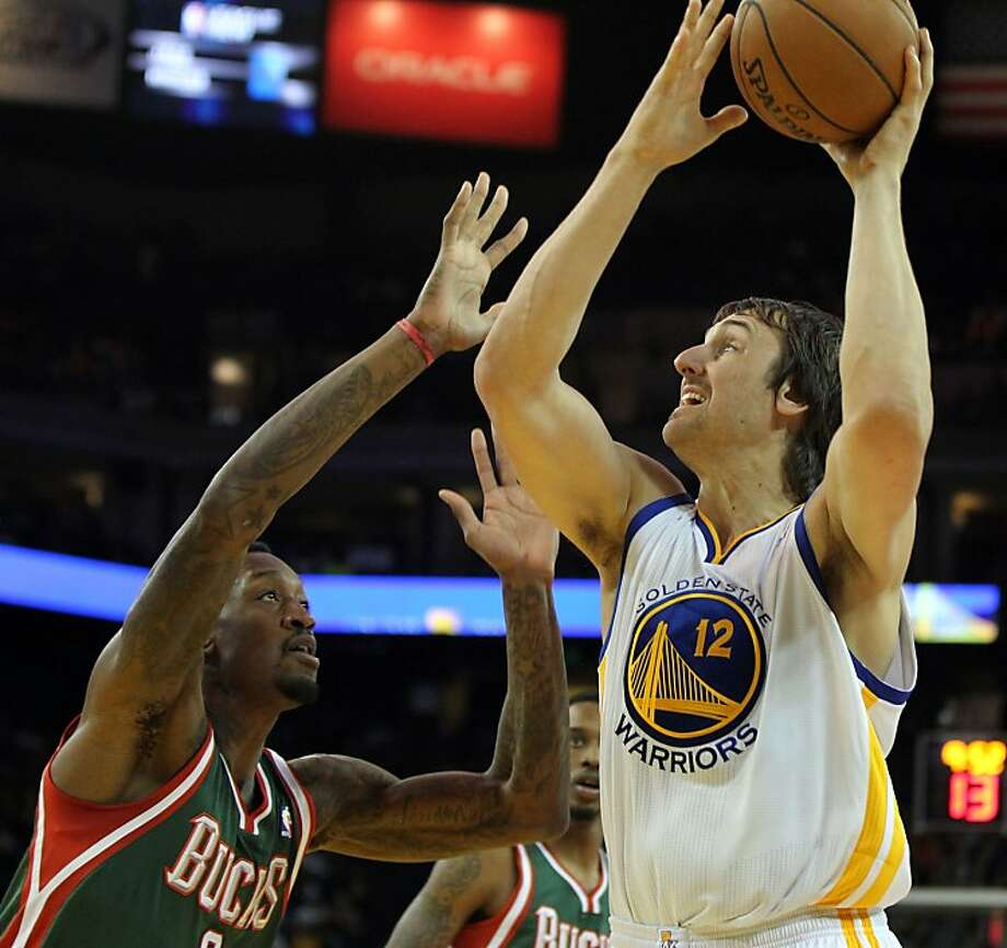 Golden State Warriors center Andrew Bogut (12) shoots over a Milwaukee Bucks defender in the first half of their NBA basketball game Saturday, March 9, 2013, in Oakland Calif. Photo: Lance Iversen, The Chronicle