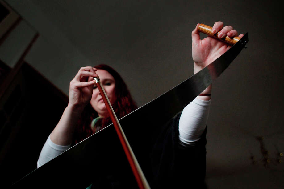 Anika Erdmann practices her musical saw playing in her living room in San Francisco, Calif. Erdmann, who has always wanted to play the saw traded her expertise in social media for a saw. Photo: Mike Kepka, The Chronicle / ONLINE_YES