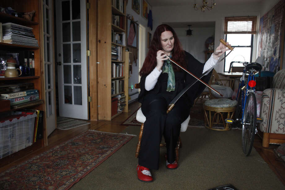 Anika Erdmann practices her musical saw playing in her San Francisco living room. She hopes some day to be able to play a song. Photo: Mike Kepka, The Chronicle / ONLINE_YES