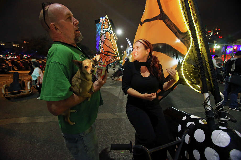 Joe Haden holds his dog Mrs. Jones as he talks with Alisha Cloud as Luminaria is held in downtown San Antonio on March 9, 2013. Photo: TOM REEL, San Antonio Express-News / San Antonio Express-News