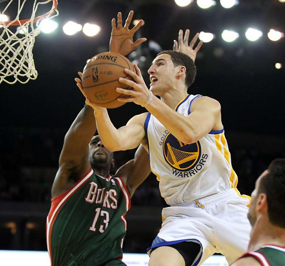 Golden State Warriors guard Klay Thompson (11) drives to the basket between two Milwaukee Bucks defenders in the second half of their NBA basketball game Saturday, March 9, 2013, in Oakland Calif. Photo: Lance Iversen, The Chronicle