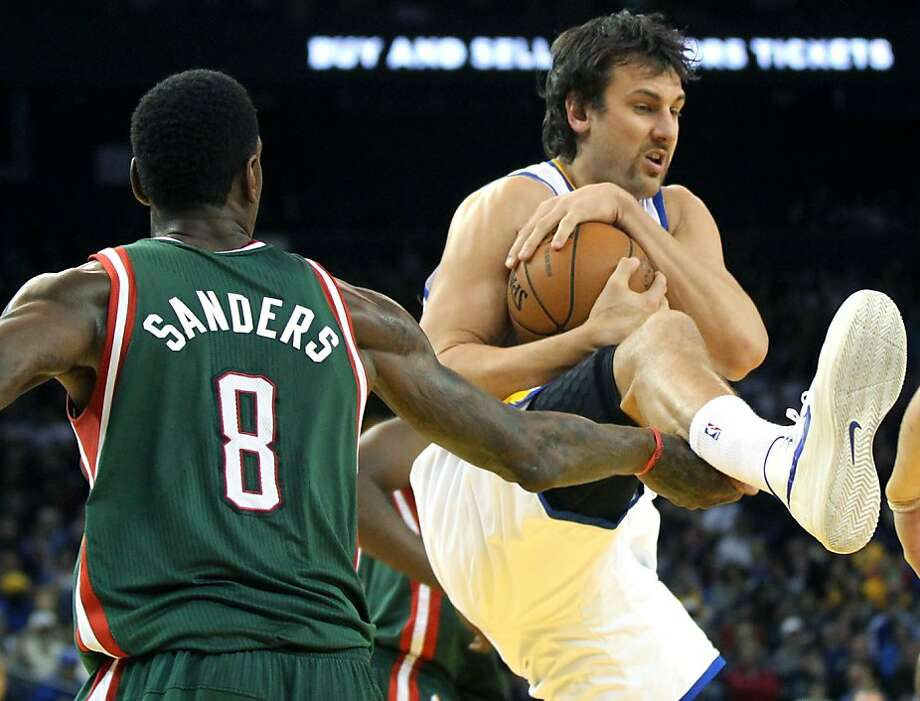 Golden State Warriors center Andrew Bogut (12) catches a rebound between two Milwaukee Bucks players in the second half of their NBA basketball game Saturday, March 9, 2013, in Oakland Calif. Photo: Lance Iversen, The Chronicle