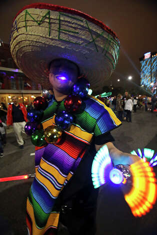 Rene Martinez walks through the festivities promoting Fiesta as Luminaria is held in downtown San Antonio on March 9, 2013. Photo: Tom Reel, San Antonio Express-News