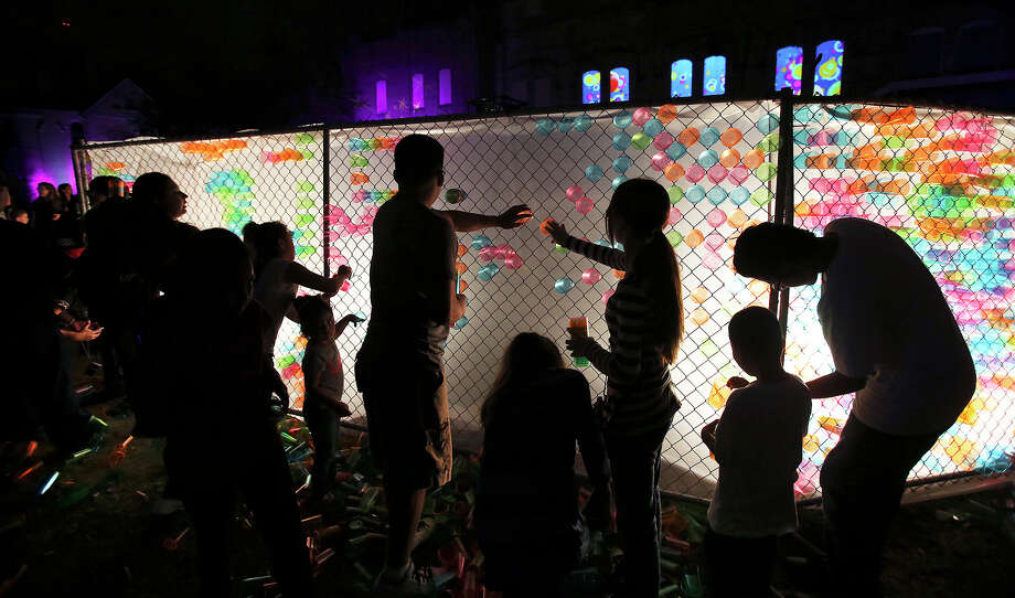 Kids produce their own artwork in a fence with translucent cups as Luminaria is held in downtown San Antonio on March 9, 2013. Photo: Tom Reel, San Antonio Express-News
