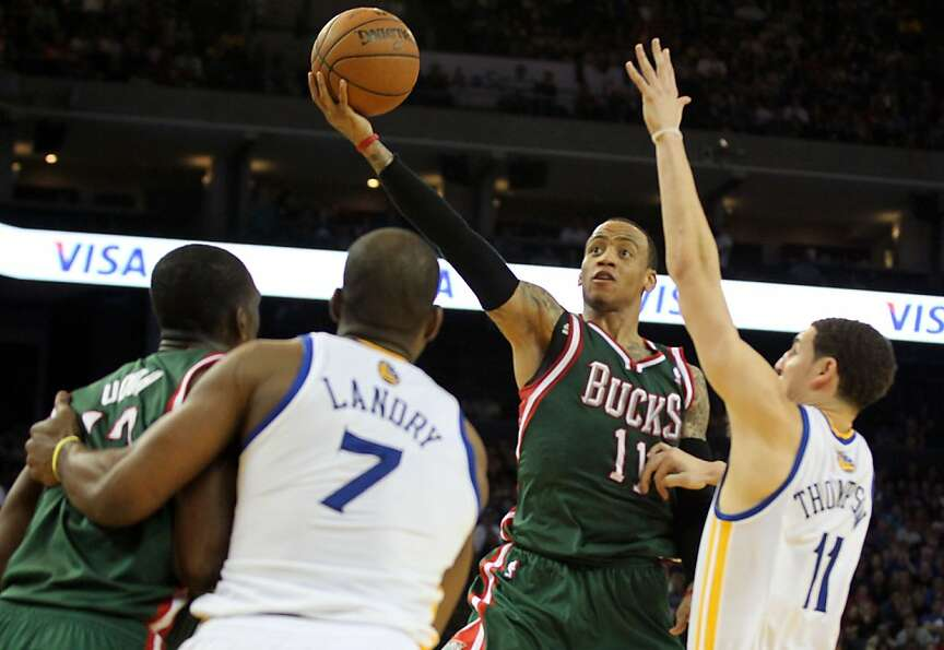 Milwaukee Bucks guard Monta Ellis scores between several Golden State Warriors defenders in the seco