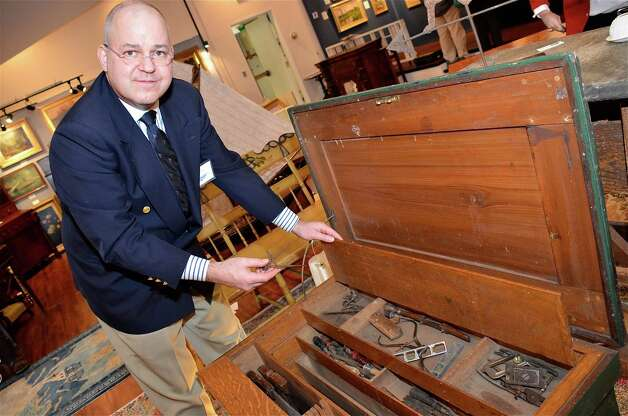 George Wilbanks of Find Weatherly Antiques picks out a caliper from inside an early 1900's Shipwright tool chest, on Saturday, March 2, 2013, at the 46th Annual Darien Antiques Show in Darien, Conn. Photo: Jeanna Petersen Shepard / Darien News freelance Jeanna Petersen Shepard