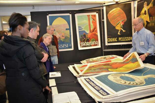 Art Finkel, of Vintage Poster Art of NJ, had plenty of customers on Saturday, March 2, 2013, at the 46th Annual Darien Antiques Show in Darien, Conn. From left to right: Sylvia Okorie, Gene Keyser, Cathy Dillon, and Dean Keister. Photo: Jeanna Petersen Shepard / Darien News freelance Jeanna Petersen Shepard