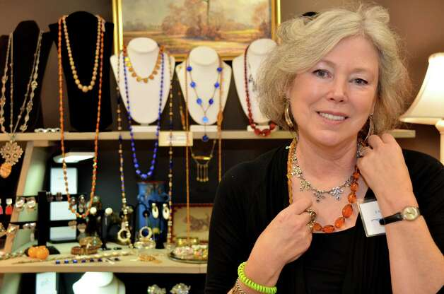 Jamie Shenkman from Jamie's Antiques, holds up an amber faceted glass necklace from the 1930's, on Saturday, March 2, 2013, at the 46th Annual Darien Antiques Show in Darien, Conn. Photo: Jeanna Petersen Shepard / Darien News freelance Jeanna Petersen Shepard