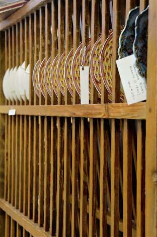 D&D Antiques from Newtown displayed an 18th-century English pine plate rack, with a row of plates to complete the look,  on Saturday, March 2, 2013, at the 46th Annual Darien Antiques Show in Darien, Conn. Photo: Jeanna Petersen Shepard / Darien News freelance Jeanna Petersen Shepard