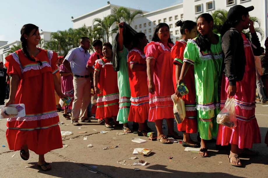 Wayuu Indian women line up outside the military academy where a funeral ceremony will take place for Venezuela's late President Hugo Chavez in Caracas, Venezuela, Friday. Friday's funeral promises to be a final turn on the world stage for Chavez after 14 years in power, though in some ways the former paratrooper is not going anywhere: Venezuela announced Thursday that it would embalm his body and put it on permanent display. Chavez died on March 5 after a nearly two-year bout with cancer.  He was 58. Photo: AP