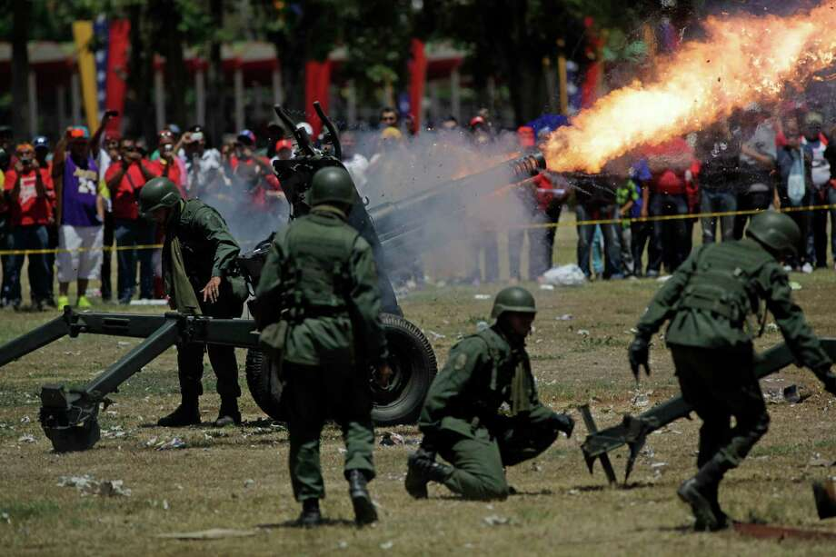Soldiers fire a canon salvo during the funeral ceremony for Venezuela's late President Hugo Chavez outside the military academy in Caracas, Venezuela, Friday. Chavez died on March 5 after a nearly two-year bout with cancer.  He was 58. Photo: AP