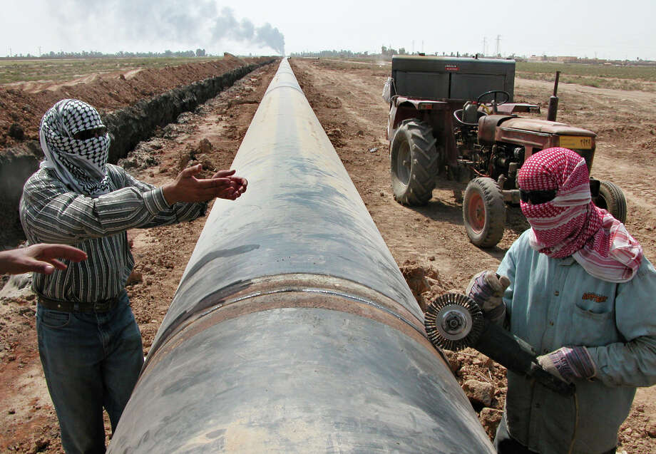 In this 2004 photo, workers lay a new natural gas pipeline after the existing one was targeted by saboteurs near Kirkuk, Iraq. Ten years and $60 billion in taxpayer funds later, Iraq is still so unstable and broken that even its leaders question whether U.S. efforts to rebuild it were worth the cost. Photo: AP