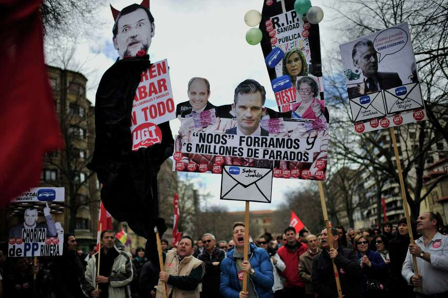 "A man carries a piece of cardboard with the portrait of Spanish Primer Minister Mariano Rajoy decorated as a devil, left, alongside portraits of Inaki Urdangarin, the Spanish's king son-in-law, center, and Former Popular Party's treasurer, Luis Barcenas, right, during a protest against austerity in Pamplona northern Spain on Sunday. One poster reads ' Noos make a mint while there are 6 million unemployed"". Tens of thousands of demonstrators are marching in dozens of Spanish cities to protest sky-high unemployment, what they say is the government's inefficient handling of the economy and corruption scandals, including one engulfing the royal family. Photo: AP"