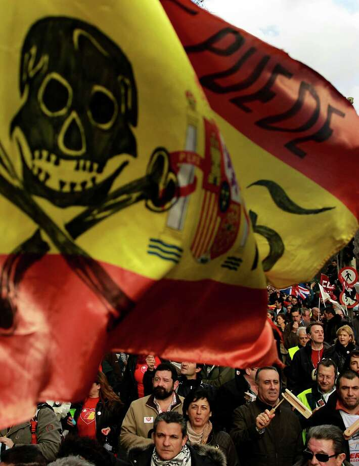 A Spanish flag with a pirate symbol on it is seen as  Iberia airline workers march during a protest in Madrid, Spain, Thursday. Spanish airline Iberia says some 1,300 flights will be canceled this week as workers begin a second round of strikes to protest the loss-making company's plans to lay off almost a fifth of its workforce. The government has ordered a minimum amount of services should remain, meaning 85 percent of long-haul flights, 62 percent of medium-haul and 47 percent of domestic flights are guaranteed. Photo: AP