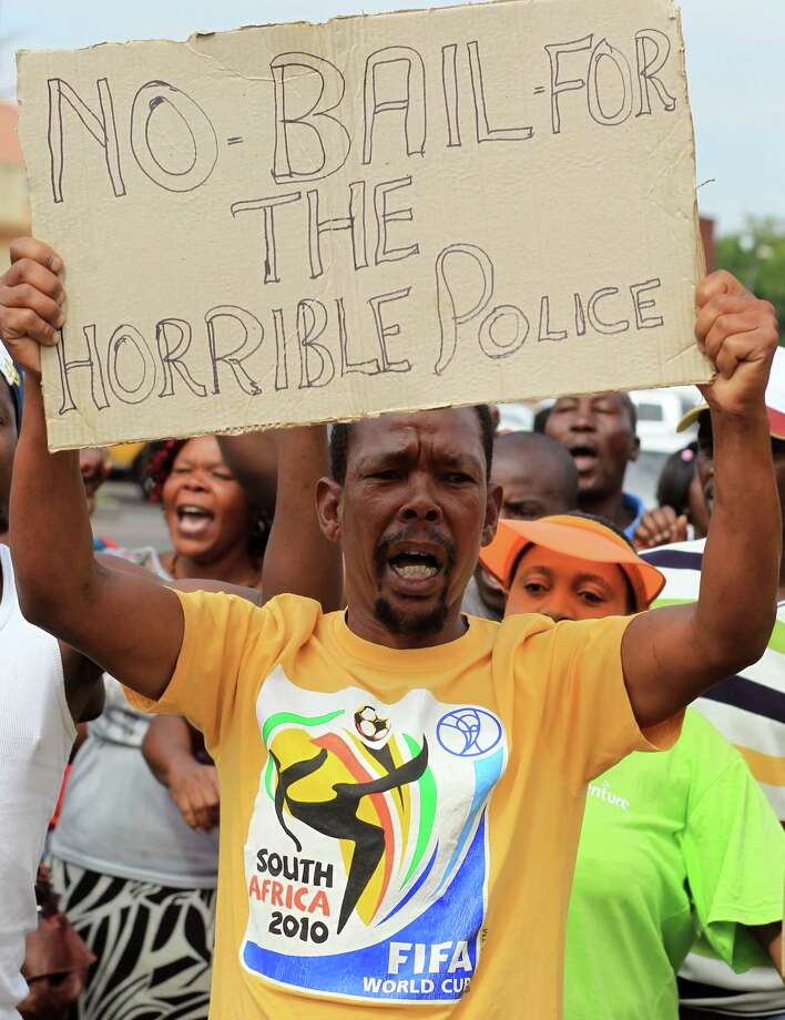A man protests  outside the courthouse  against the granting of bail  for the eight police officers charged with murdering a taxi driver Mido Macia who was dragged from a police vehicle last week in Benoni outside Johannesburg, South Africa, Friday. The killing of Mido Macia, a taxi driver from Mozambique who died in police custody on Feb. 27, shocked South Africans and viewers around the world after graphic video footage of him being tied to a vehicle by uniformed officers and dragged down a street was broadcast and posted online. Photo: AP