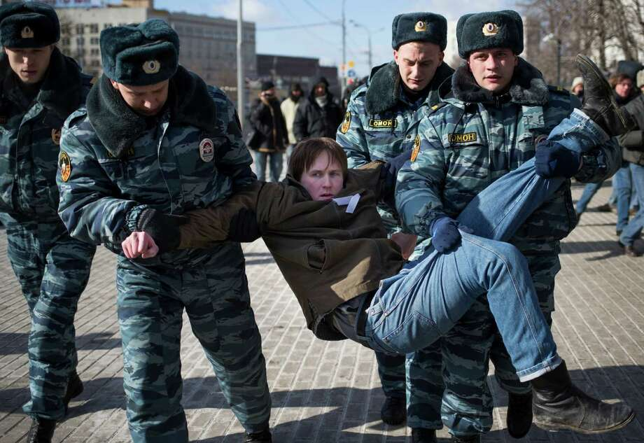 Russian police officers detain a supporter of jailed feminist punk band Pussy Riot members during a protest in Moscow,  Russia, Friday. Photo: AP