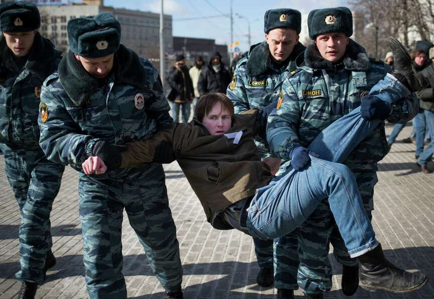 Russian police officers detain a supporter of jailed feminist punk band Pussy Riot members during a