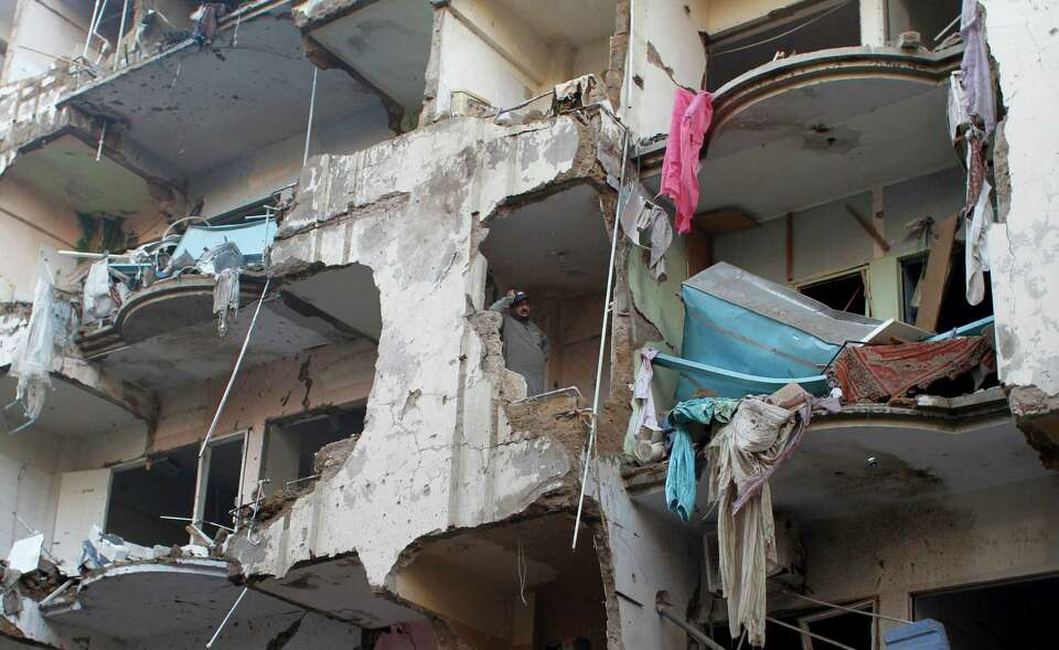 A Pakistani man stands in a damaged apartment which was destroyed along with other buildings in a Su