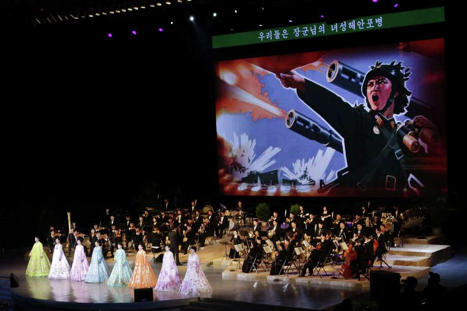 "An image depicting a female North Korean soldier leading an artillery attack is projected on a large screen behind singers and the Unhasu Orchestra during a concert to mark International Women's Day in Pyongyang, North Korea, on Friday. The text at the top of the screen reads, ""We are the General's female coastal artillery troops."" Photo: AP"