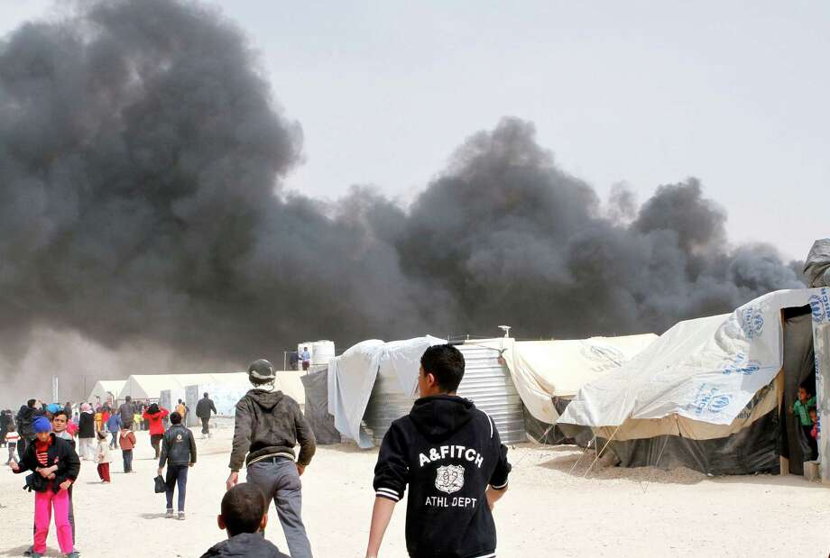 Syrian refugees watch as a fire sends black smoke rising over the Zaatari  refugee camp in northeast Jordan, Friday. The U.N. refugee agency says a fire broke out in Jordan's Zaatari camp for Syrian refugees but reported no major injuries or deaths in the blaze that burned at least 20 or more tents, including some hosting small shops. Photo: AP