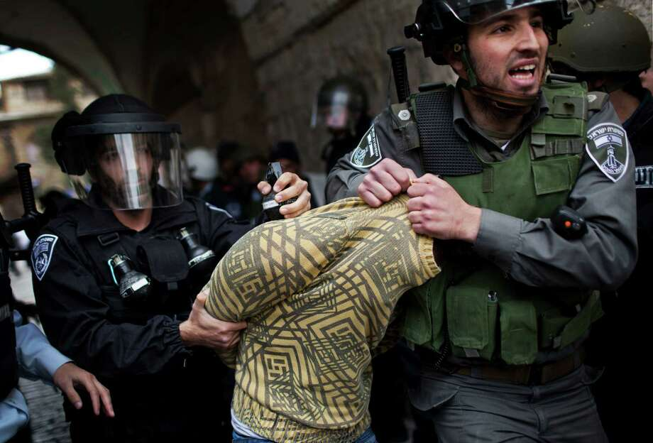 A Palestinian man is detained by Israeli security forces in Jerusalem's Old City, Friday. Clashes erupted between Palestinian worshippers and Israeli forces during Friday prayers at the Al Aqsa Mosque compound. The contested site, where the Al-Aqsa Mosque compound is built above the ruins of the biblical Jewish Temples, is one of the region's most sensitive. Israeli steps to quell Palestinian disturbances there have led to full-blown riots in the past. Photo: AP