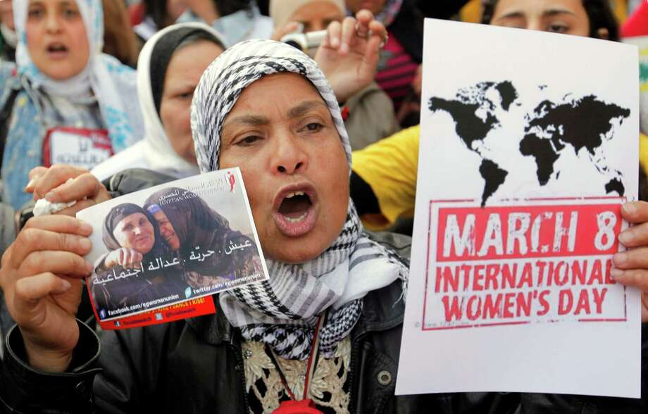 "An Egyptian woman shouts anti- Muslim Brotherhood slogans during a demonstration in Cairo, Egypt, Friday marking International Women's Day. Arabic reads, ""bread, freedom, social justice."" Photo: AP"