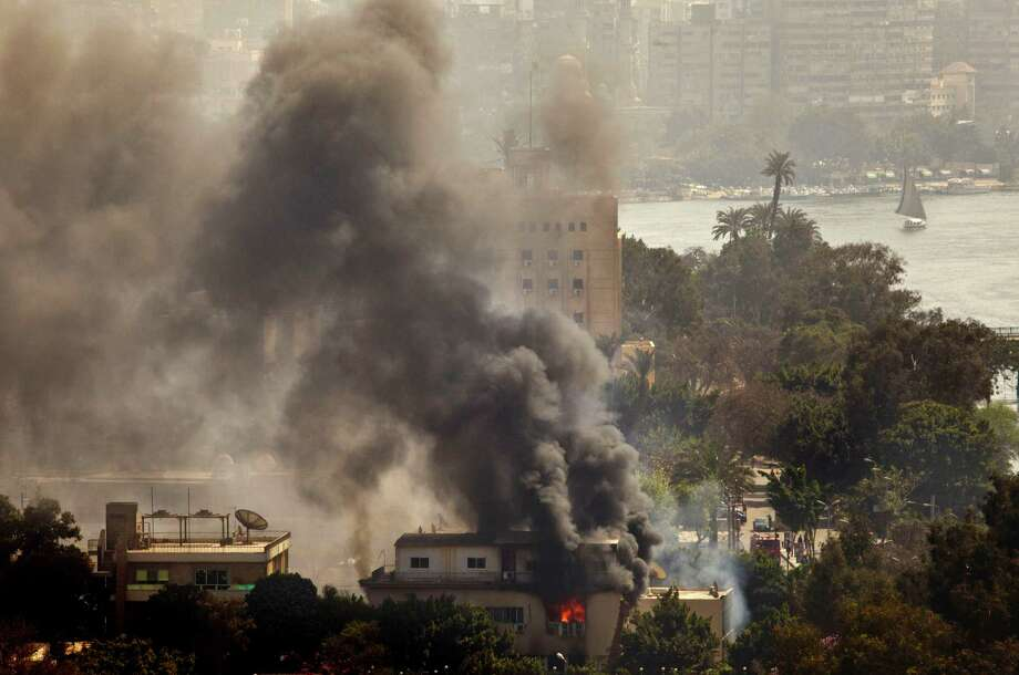 Smoke and fire rises from the Egyptian Soccer Federation after protesters set fire following a court verdict in, Cairo, Egypt, Saturday, March 9, 2013. An Egyptian court on Saturday confirmed the death sentences against 21 people for taking part in a deadly soccer riot but acquitted seven police officials for their alleged role in the violence. Suspected fans enraged by the verdict torched the soccer federation headquarters and a police club in Cairo in protest. Photo: AP