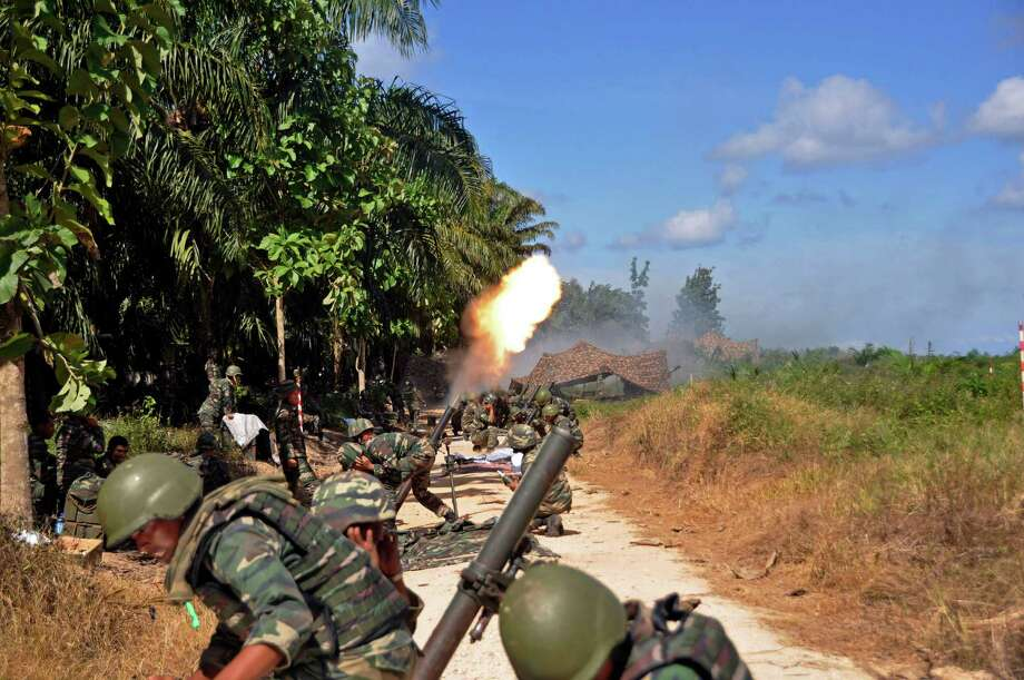Malaysian soldiers fire mortars Friday toward the area where a stand-off with Filipino gunmen took place, at Tanduo village in Lahad Datu, Borneo's Sabah state, Malaysia. Malaysian police said Saturday they had detained 79 suspects linked to Filipino intruders in Borneo as they intensify an operation to flush out members of a Filipino Muslim clan who took over a village last month. (AP Photo/Malaysia's Ministry of Defense)  Photo: AP