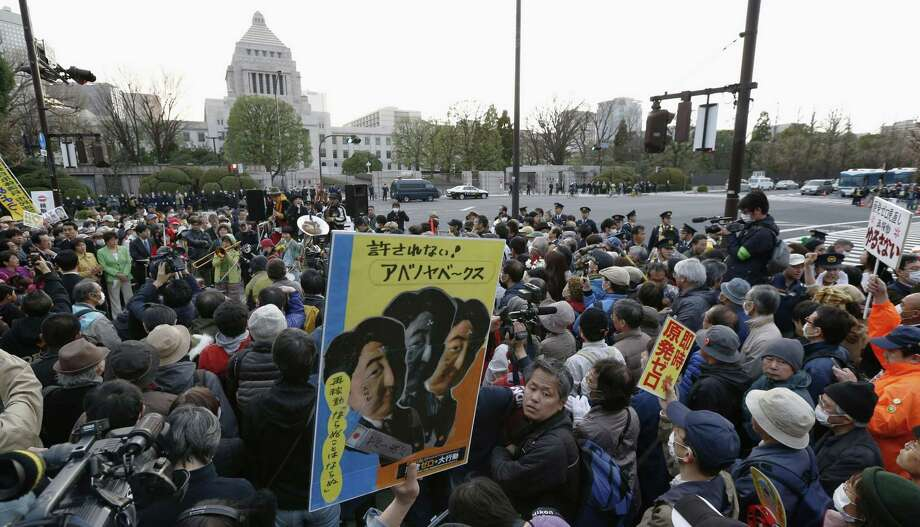 Protesters hold an anti-nuclear demonstration in front of the National Diet building, background center, in Tokyo Sunday. Thousands of people gathered in downtown Tokyo, marching to the prime minister's official residence and the National Diet in protest against the government's nuclear policy.  Japan will mark the second anniversary of the March 11, 2011 earthquake and tsunami on Monday. (AP Photo/Kyodo News)  Photo: AP