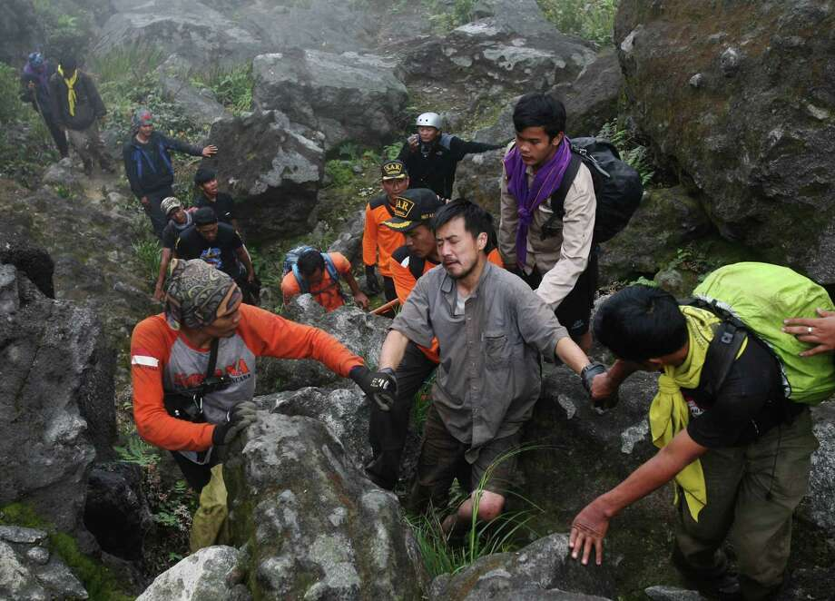 Japanese mountaineer Kosei Yamada, center, who was reported missing on Wednesday last week, is assisted by rescuers after he was found at the bottom of a ravine at Mount Sibayak in Karo, North Sumatra, Indonesia, Sunday. Yamada was found alive near the top of the 7,257 ft active volcano. Photo: AP